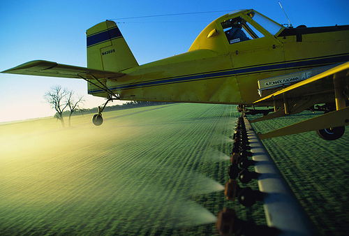 Crop Duster Flying Over Fields
