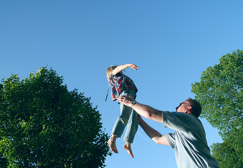 Man Tossing Child in Air