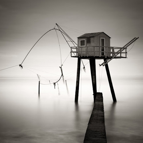 fishing shack with pier, long exposure mono square by Michel Rajkovic
