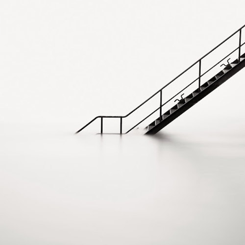 Long exposure photo of staircase leading into water in mono square format - by Michel Rajkovic
