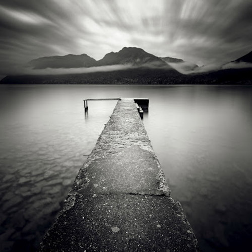 Long exposure of pier extending out onto a lake with incredible mountains in the distance, in mono square format - by Michel Rajkovic
