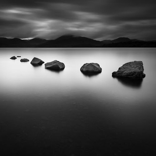 Long exposure of lake with rocks in foreground, mountain range in background, mono square - by Michel Rajkovic