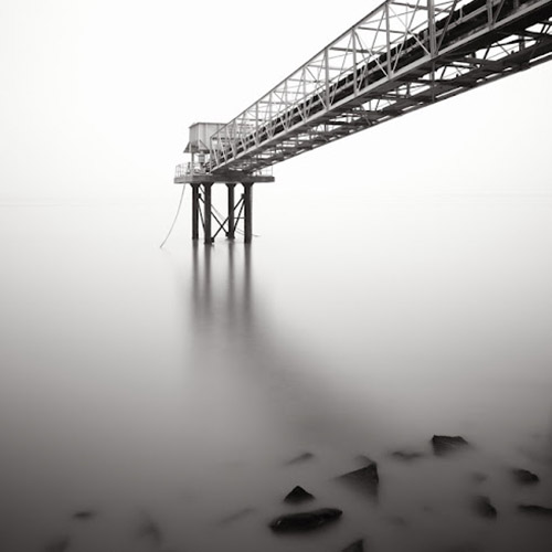 Long exposure of bridge over water, with rocks in the foreground, in mono square format - by Michel Rajkovic