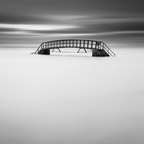 Long exposure photo of ocean and bridge, mono square format - by Michel Rajkovic