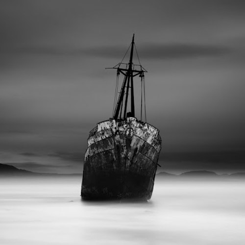 Long exposure photo of abandoned ship in ocean in mono square format - by Michel Rajkovic