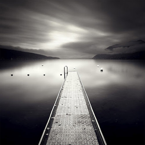 Long exposure photo of pier extending out onto a lake, in mono square format - by Michel Rajkovic
