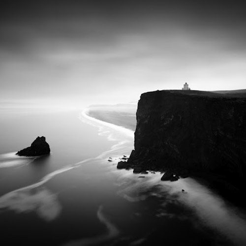 Long exposure photo of cliffside with lighthouse and ocean in mono square format - by Michel Rajkovic