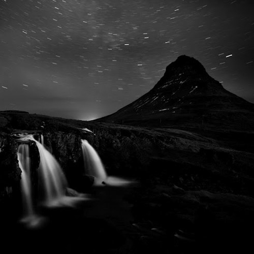 Long exposure night shot of waterfall and mountain, with starry sky in the background, in mono square format - by Michel Rajkovic