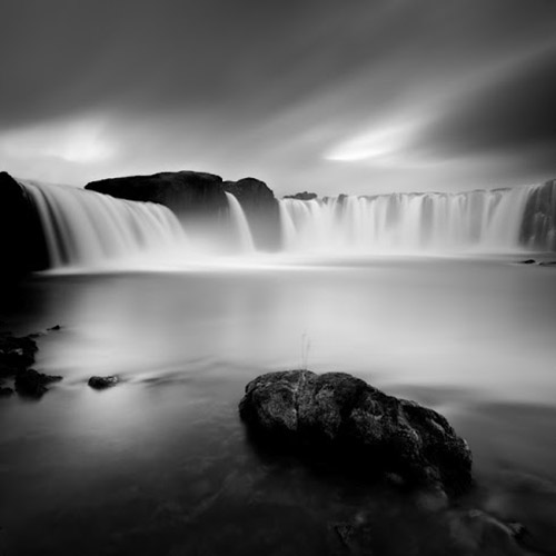 Long exposure of massive waterfall with large rock in foreground, in mono square format - by Michel Rajkovic