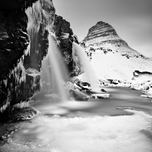 long exposure landscape of waterfall in winter; ice and mountains in background - by Michel Rajkovic