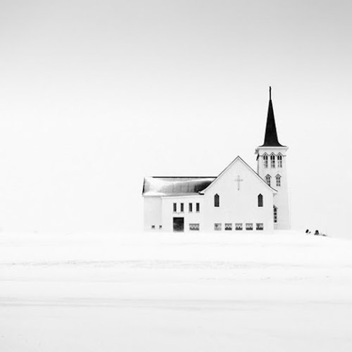 Black and white photo of church in snow, minimal high contrast image in mono square format - by Michel Rajkovic