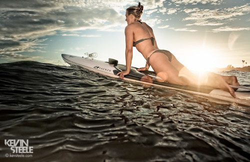 A young woman on a paddleboard at sunset in Santa Barbara, CA