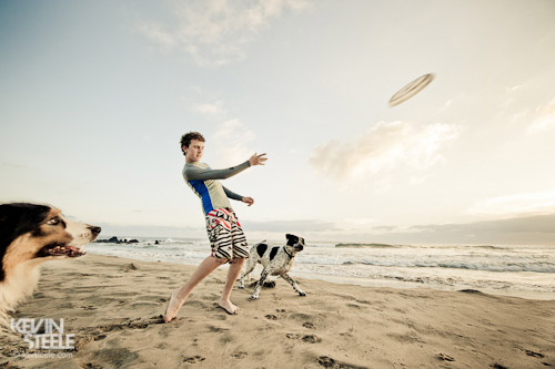 A teenage boy tosses a frisbee for two eager dogs on a quiet beach in Mexico.
