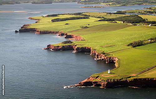 An aerial view of Cape Tryon lighthouse and the green coastline of Prince Edward Island, Canada