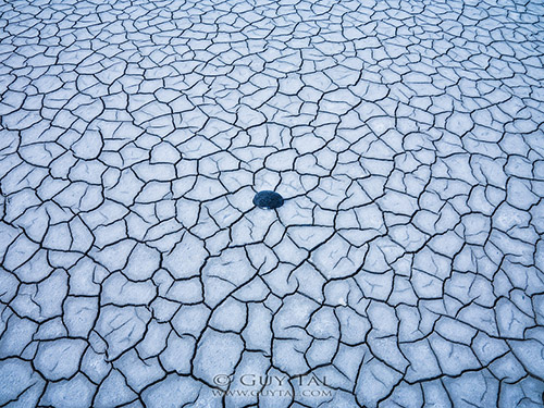 """Centerpoint"" by landscape photographer Guy Tal; a stone centered among the cracked sand"