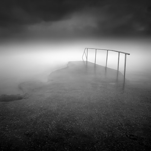 fog and mist surround a railing along the ocean, mono square format, by Julia Anna Gospodarou