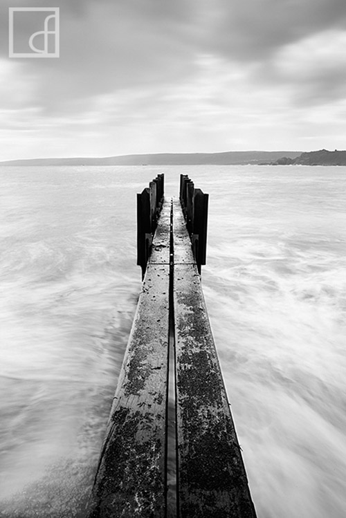 Long exposure photo of a hand-made pier jutting out onto the water with coastline in the distance