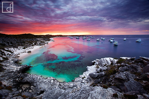 The rocky coastline of Australia, with deep turquoise water and purple skies.