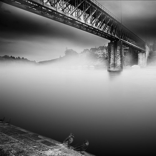 Large suspension bridge covered with mist and fog; long exposure in black and white.