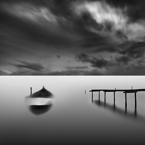 Row boat moving with the tide, next to a stark-looking pier; long exposure in black and white