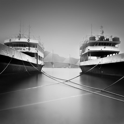 Two shipping vessels side by side, with their dock lines intertwined - long exposure, black and white.