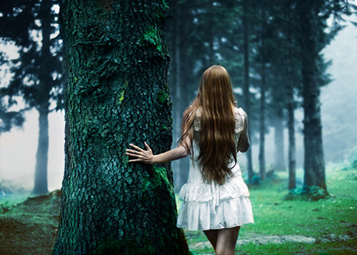 A young girl stands next to a giant tree, looking into the deserted forest.