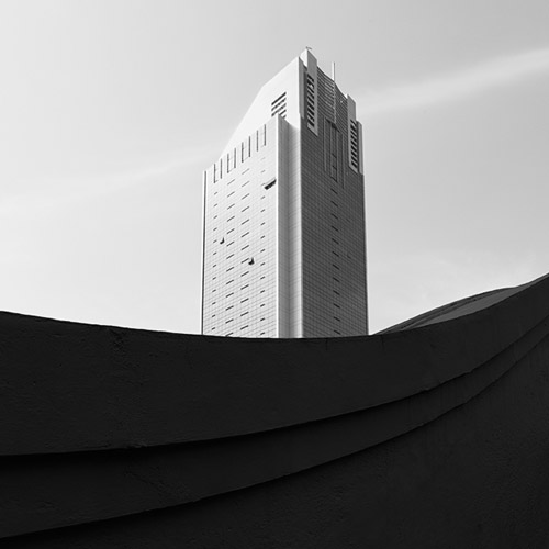 Skyscraper against the bright sky with strong lines, black and white fine art photography.