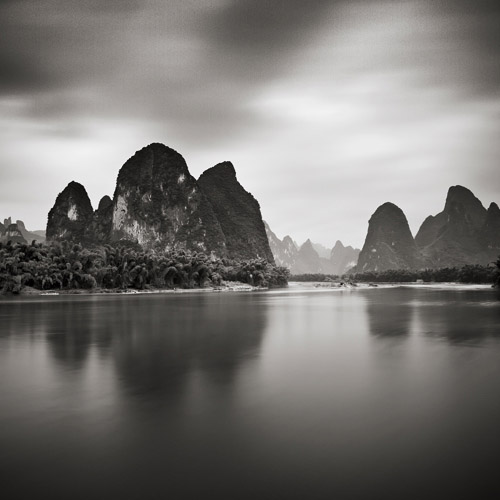 Tall rocks protrude in the background behind a lake, fine art black and white photography.