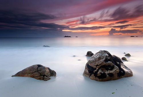 Two rocks sit in a cream ocean under a dramatic stormy sky.