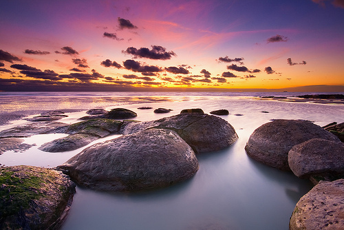 Smooth rocks with a colorful sunset.