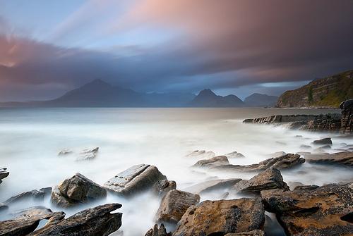 Long exposure coastline with dramatic mountains, by Nicolas Rottiers.