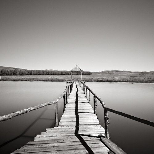 Long pier leads out onto the water, fine art black and white photography.