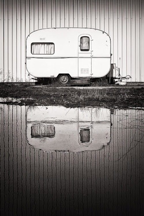 Caravan parked along the water with its reflection, black and white.