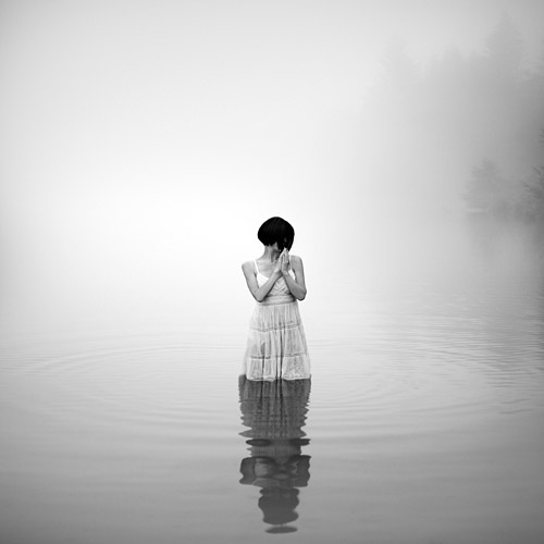 A woman stands still in a lake, arms crossed and looking down; fine art photography by Ebru Sidar