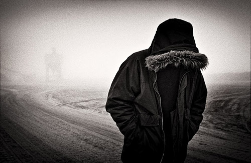 Man covered by hooded jacket, walking with face down along a deserted road.