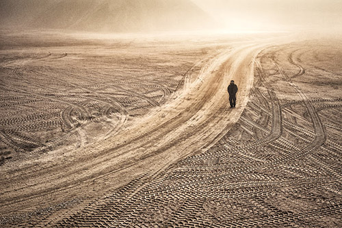 A man walks through a dirt landscape with a path etched out by traffic.