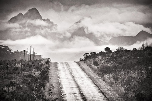 Deserted road leading to a mountain vista submerged in deep fog