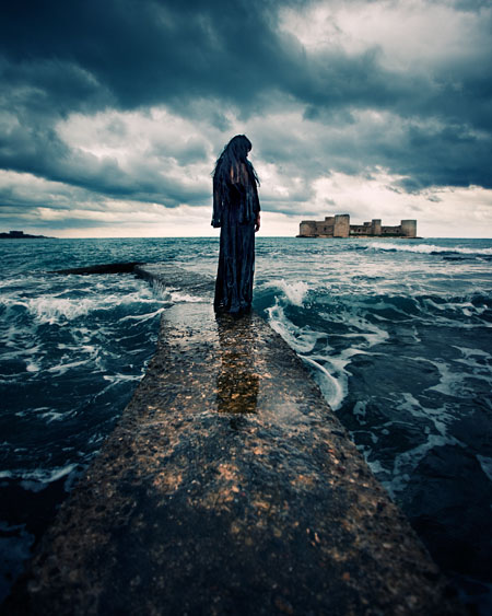 Woman stands clothed in black along the water; fine art photography by Ebru Sidar