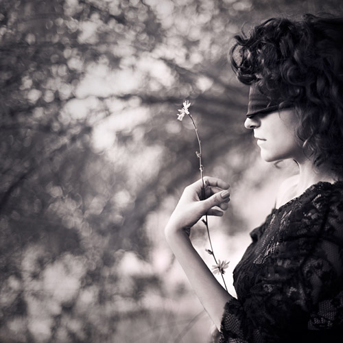A woman looks at a flower while blindfolded; fine art photography by Ebru Sidar