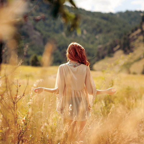 A woman with fire red hair wanders through a field of wheat