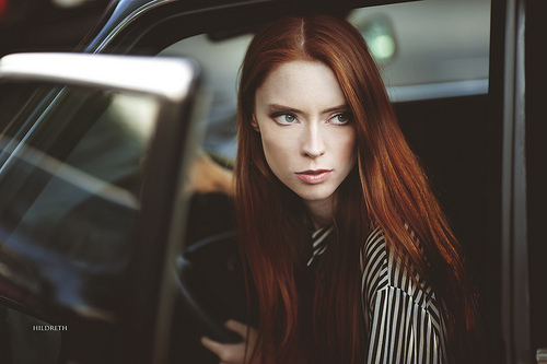 A red-haired woman gazes out her car as she exits