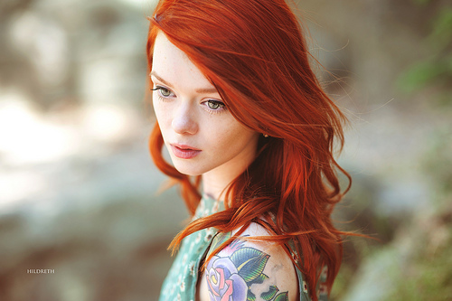 A tattooed red head looks into the distance, pensive.