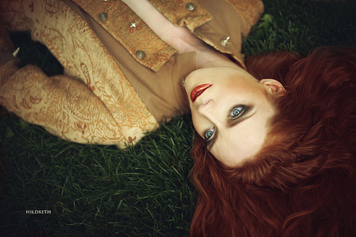 A beautiful red-haired woman lies on a carpet of green grass.