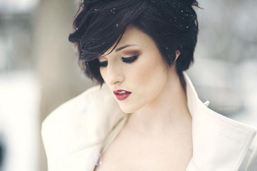 A black-haired woman stares down towards the ground in a blanket of snow - fine art photography by Charles Hildreth