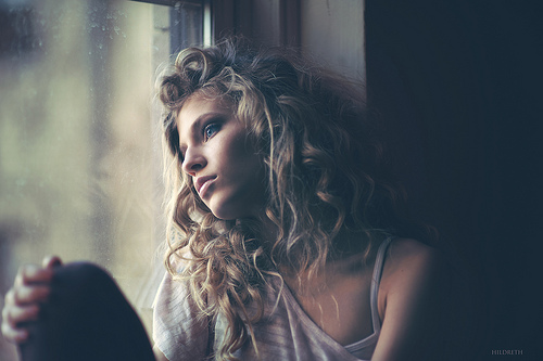 A woman with long blonde curls gazes out a window deep in thought - fine art portrait by Charles Hildreth
