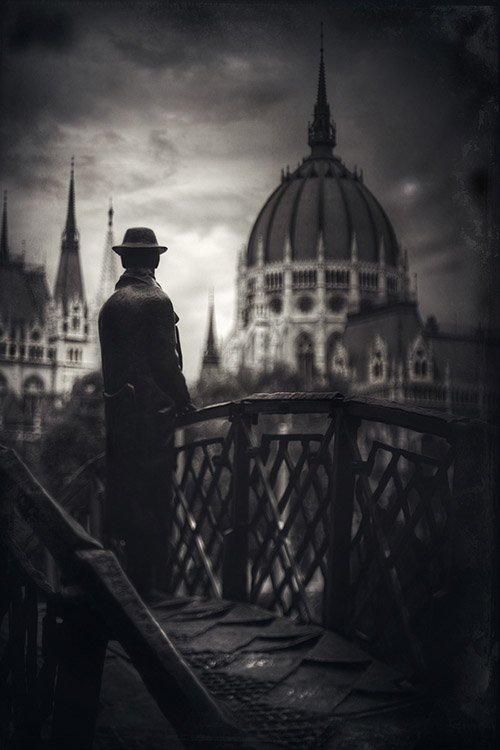 A man gazes at the city of Budapest from a footbridge