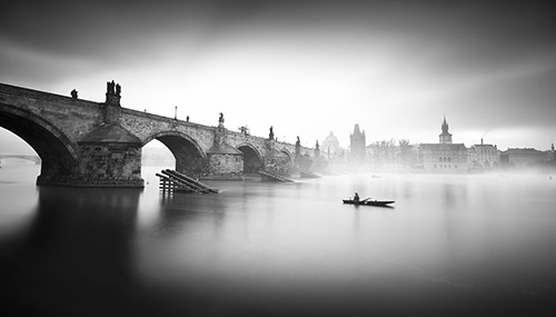 The Charles Bridge in Prague under a blanket of thick fog.