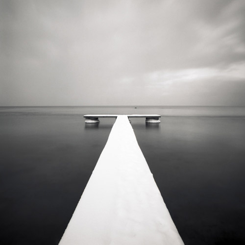 Snow covered pier over water, black and white photography by Hakan Strand