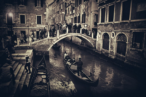 A gondola passes under a small footbridge filled with people in Venice