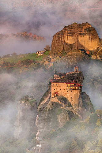 Suspended in Light - houses on a cliffside with mist